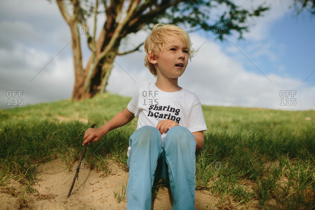 A boy sits on a sand dune
