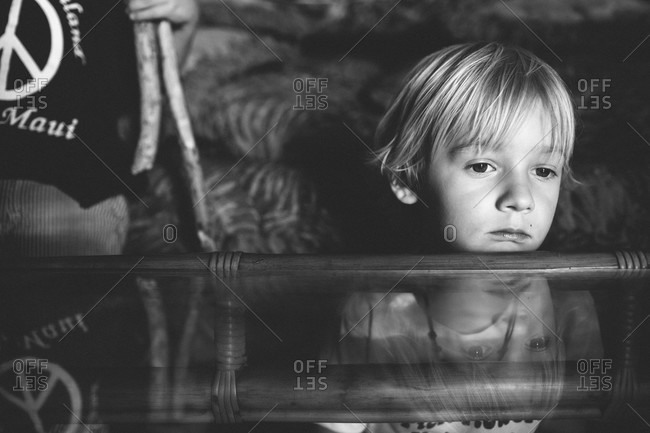 A boy sits on the floor next to a coffee table