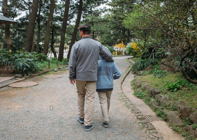 Boy and man walking through park in Japan