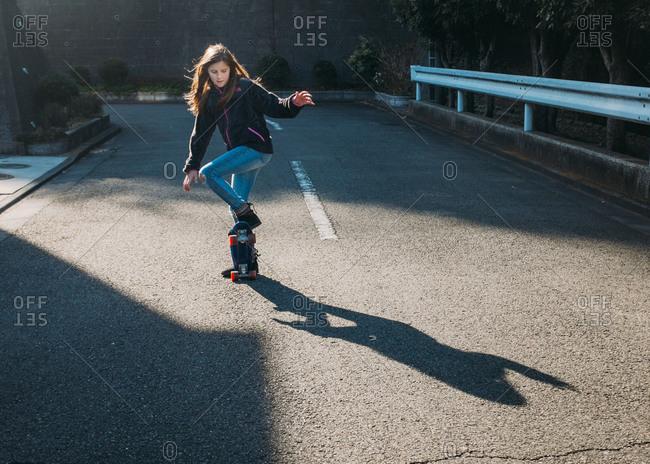 Girl doing trick on skateboard on side street