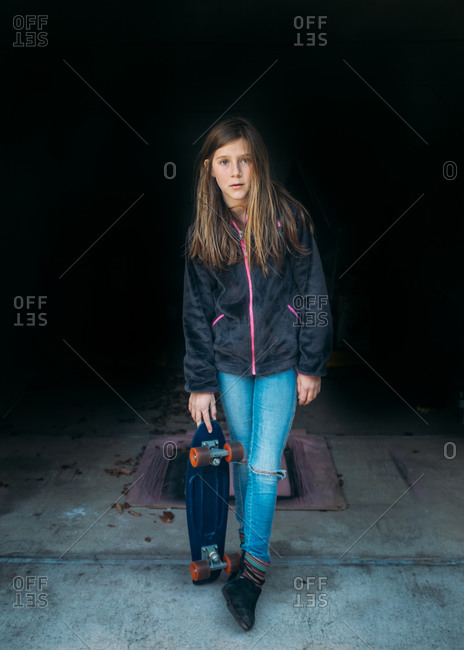 Girl standing with skateboard with black background
