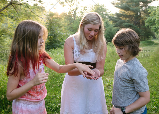 Three kids in country looking at frog