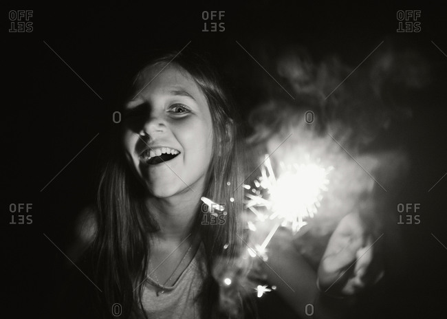 Portrait of girl laughing with sparkler