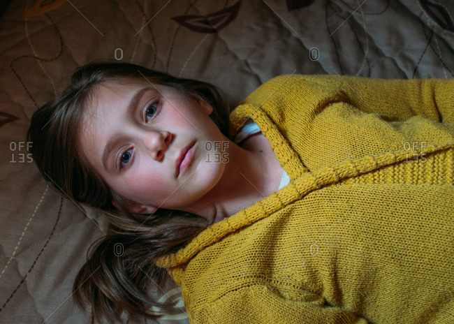 Girl in cardigan lying face up on bed