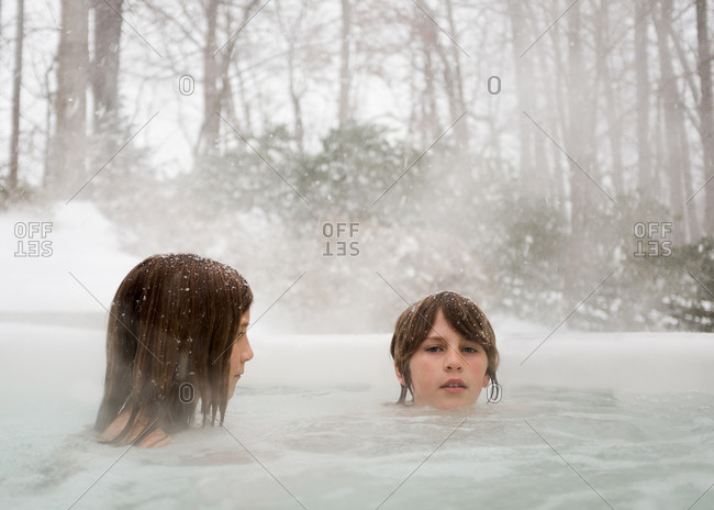 Two kids in a hot tub in winter