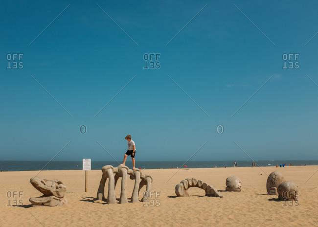 Ocean City, Maryland - July 1, 2015: Boy walking on dinosaur bone sculpture on beach