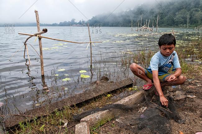 Bratan Lake, Indonesia - May 29, 2015: A young boy fishing