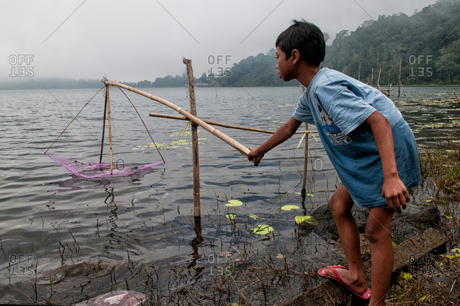 Bratan Lake, Indonesia - May 29, 2015: Young boy fishing with a rod
