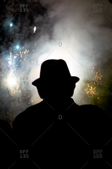 A man in a hat watches Fourth of July fireworks
