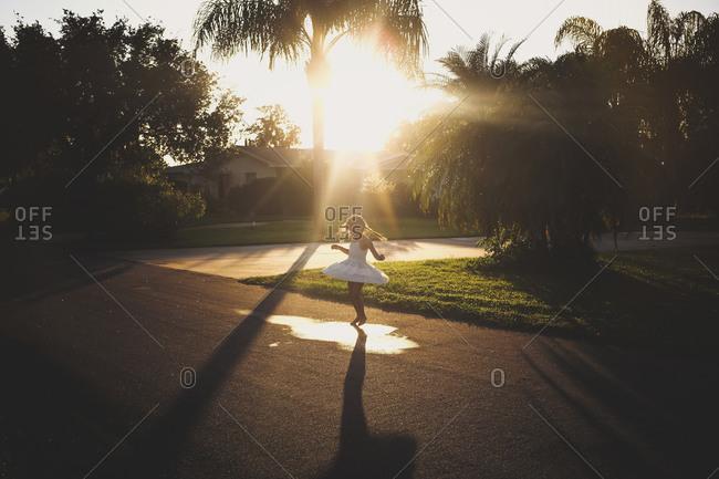 Little girl twirling at sunset