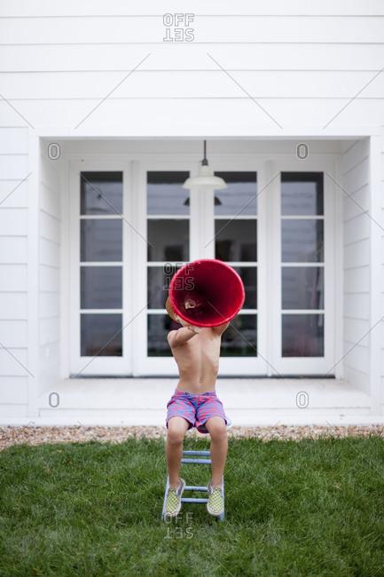 A boy uses a red megaphone
