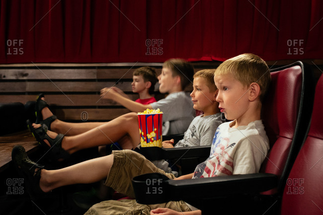 Four boys in theater seats with popcorn