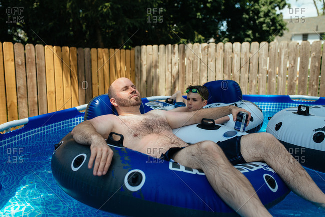 Boy and man lying on floaties in pool