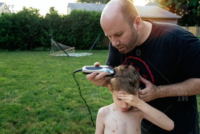 Man using clippers to trim boy's hair