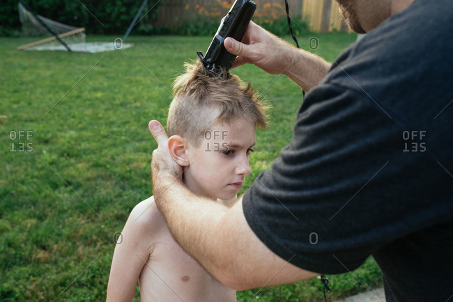 Man using clippers to trim boy's hair outside