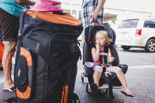 A little girl sits in a car seat in a rental car parking lot