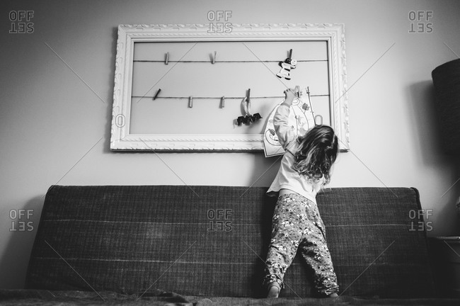 A girl hangs up a drawing with clothespins