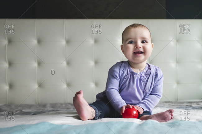 A baby sits on a bed and giggles