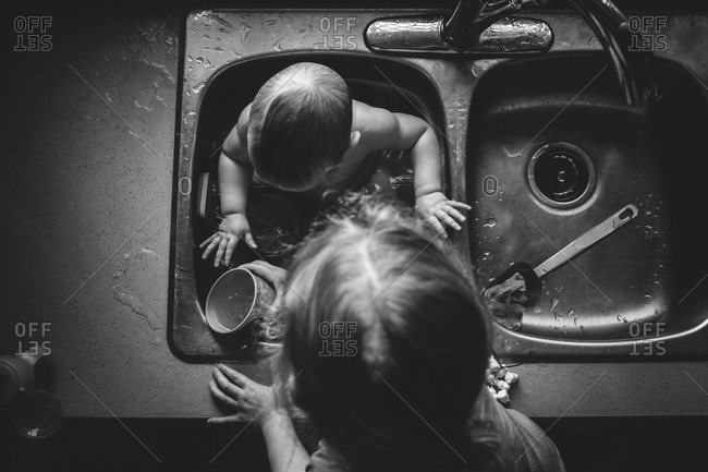 A sister helps bathe her sister in the kitchen sink