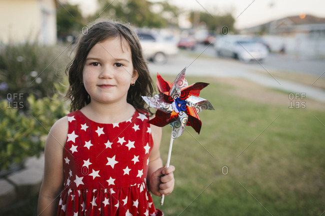 Young girl in patriotic dress holding a red white and blue pinwheel