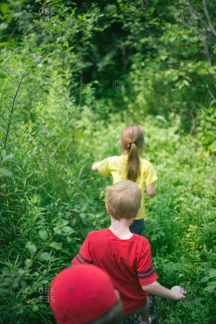 Children walking through dense plant life