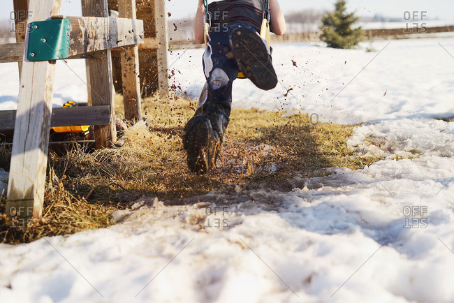 Boy kicking up mud and snow on a swing set