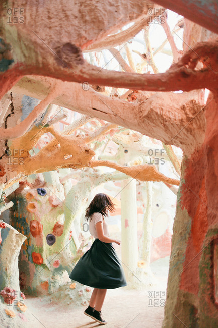 A young woman dances amid painted trees