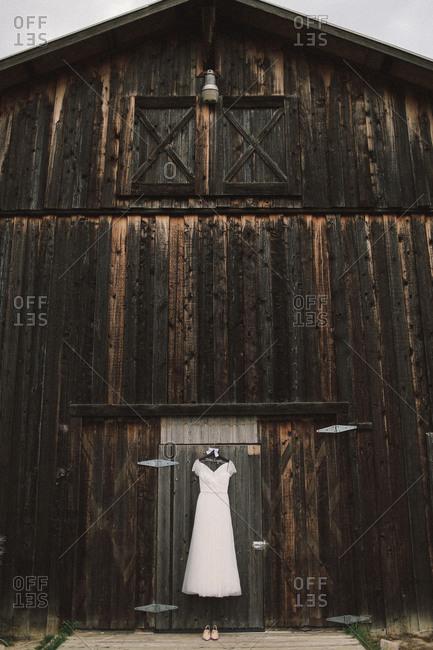 A wedding dress hangs on a barn door
