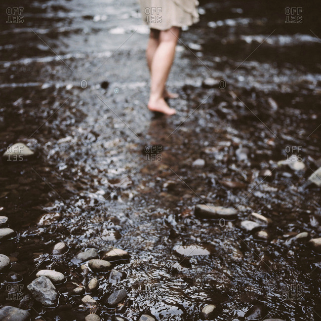 A woman walks barefoot in a stream