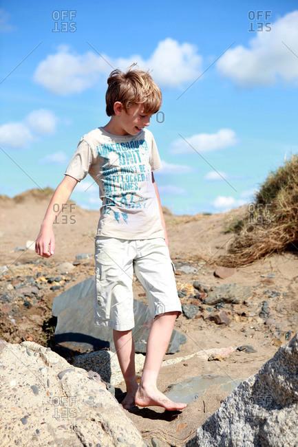 A boy walks on a rocky beach