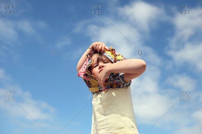 A girl takes off his shirt under a blue sky