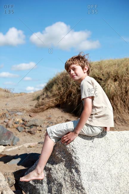 A boy walks on a rocky at the beach
