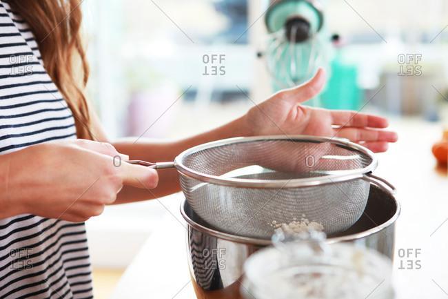 A woman sifts flour