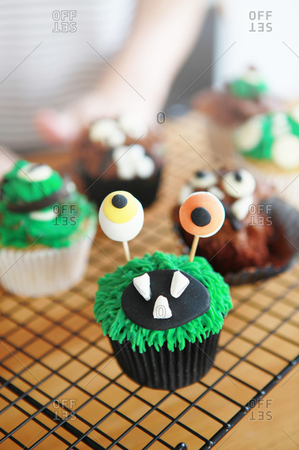 Cupcakes decorated as monsters on a cooling rack