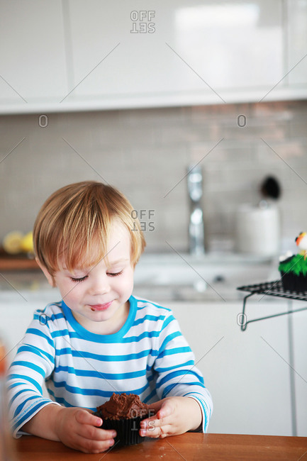A boy eats a chocolate cupcake in the kitchen