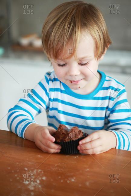 A boy eats a chocolate cupcake on kitchen counter