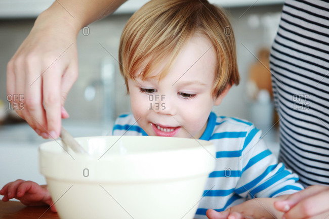 A son watches his mother baking
