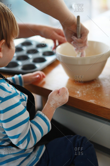 A mother shows her son how to bake cupcakes