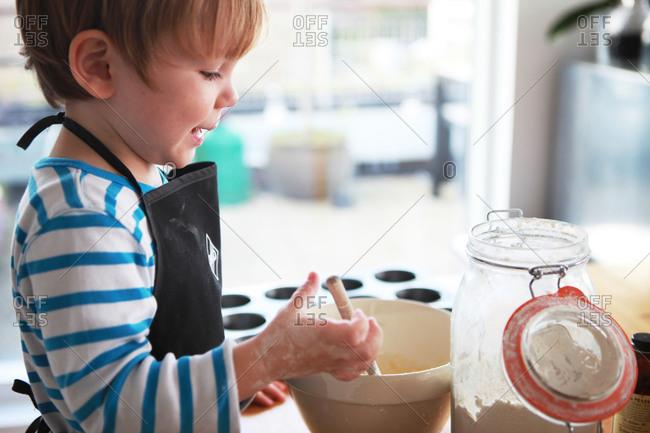 A boy in an apron bakes cupcakes