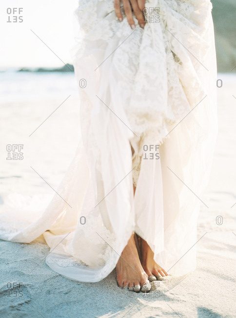 A bride stands barefoot on a beach