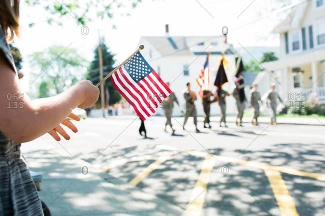 Girl holding American flag watching parade