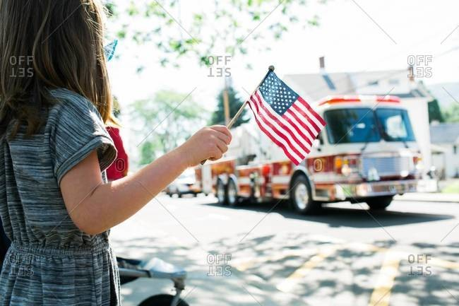 Girl with American flag watching parade