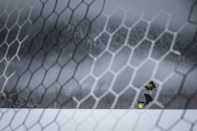 Woman kicking up soccer ball in snowy field