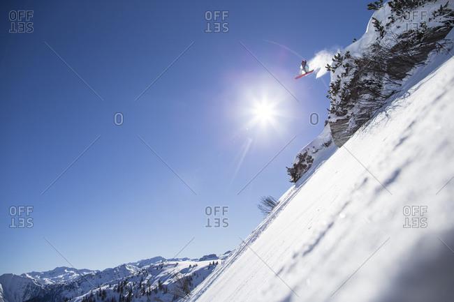 Snowboarder jumping off high mountain peak