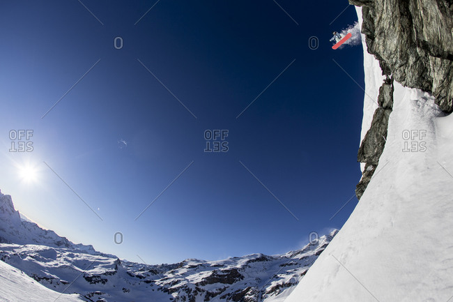 Snowboarder going off high mountain jump
