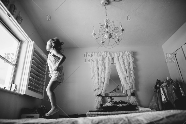 10ec1c94 Little girl jumping on her bed stock photo - OFFSET