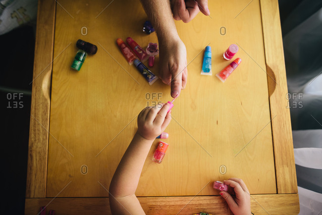 Child applying nail polish to an adult's fingernails
