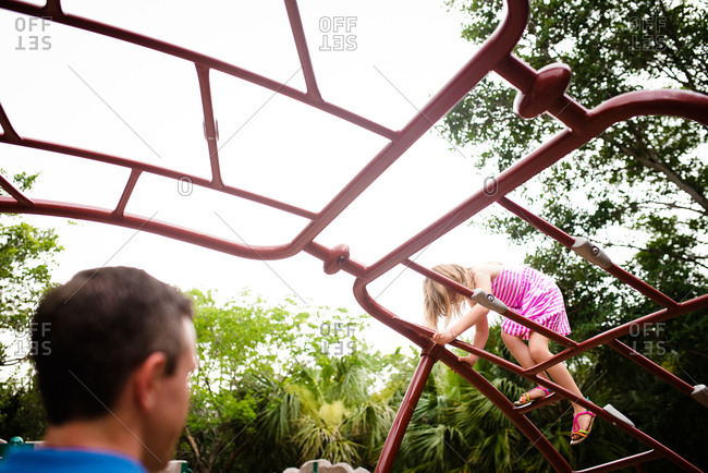 Father supervising his daughter climbing on a jungle gym