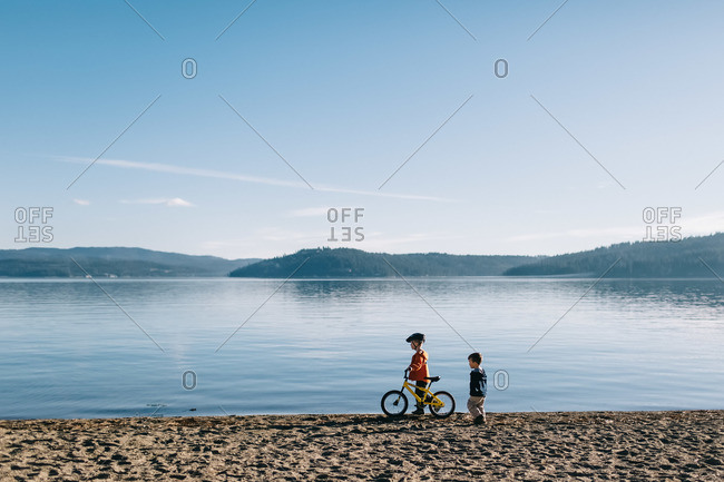 Two boys with a bicycle at the lakeshore