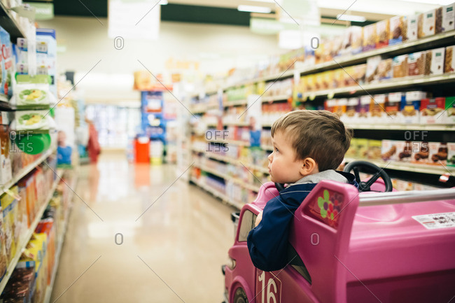 A boy rides in the toy car of a shopping cart